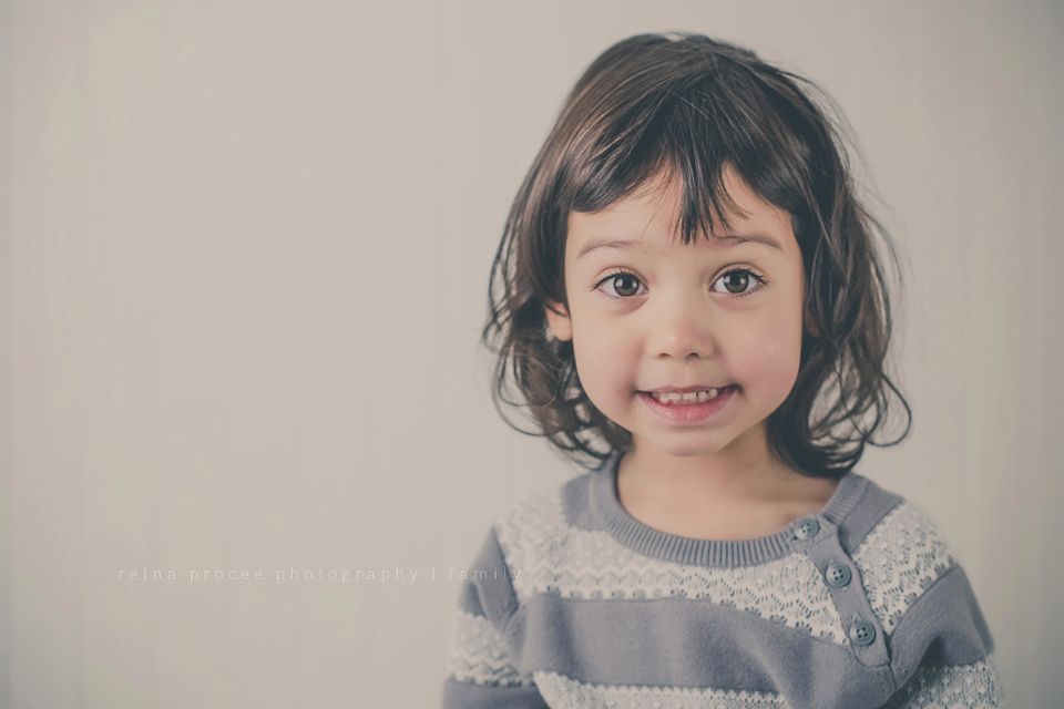 little girl in grey sweater smiling for camera