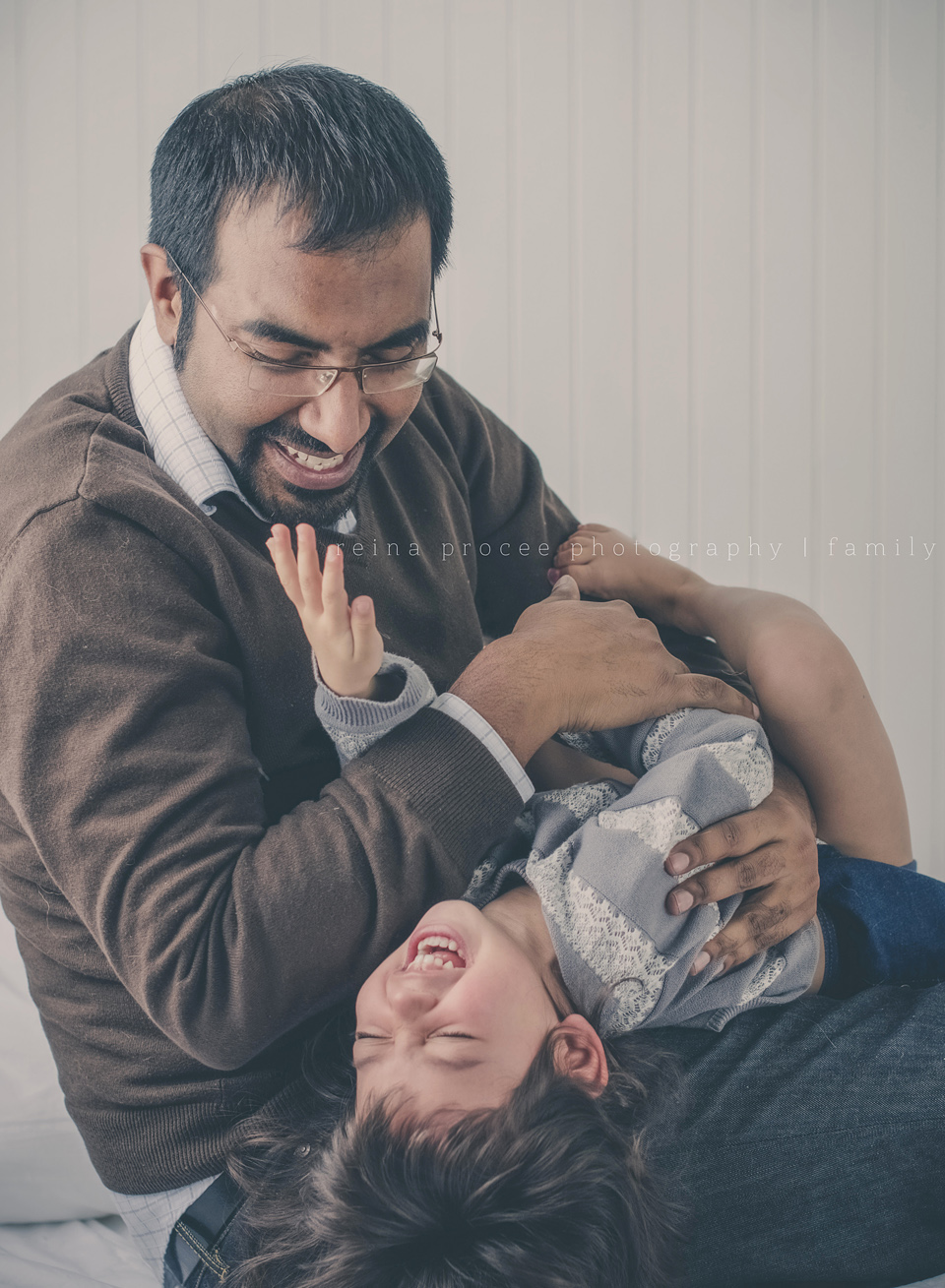 father tickling three year old daughter