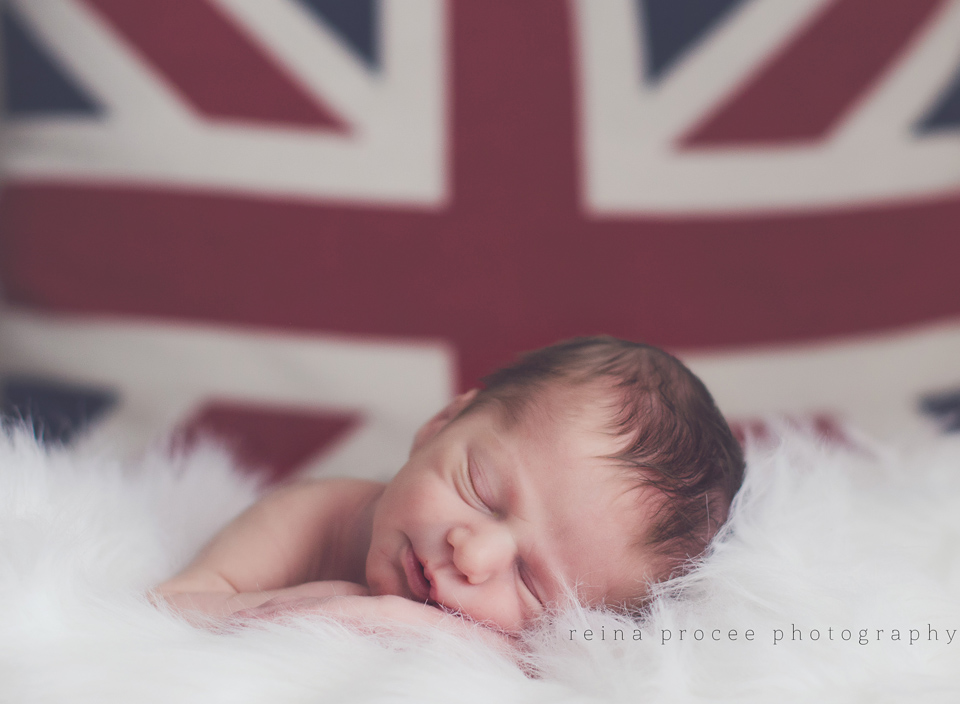 baby boy sleeping in white fur with british flag behind him