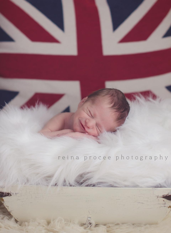baby boy sleeping with british flag behind him smiling