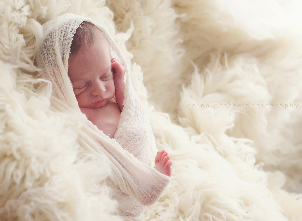 baby boy swaddled in white  with beige fur