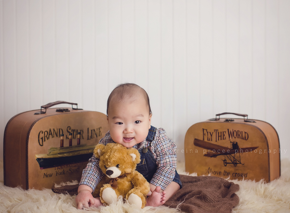baby boy sitting between vintage suitcase holding teddy bear