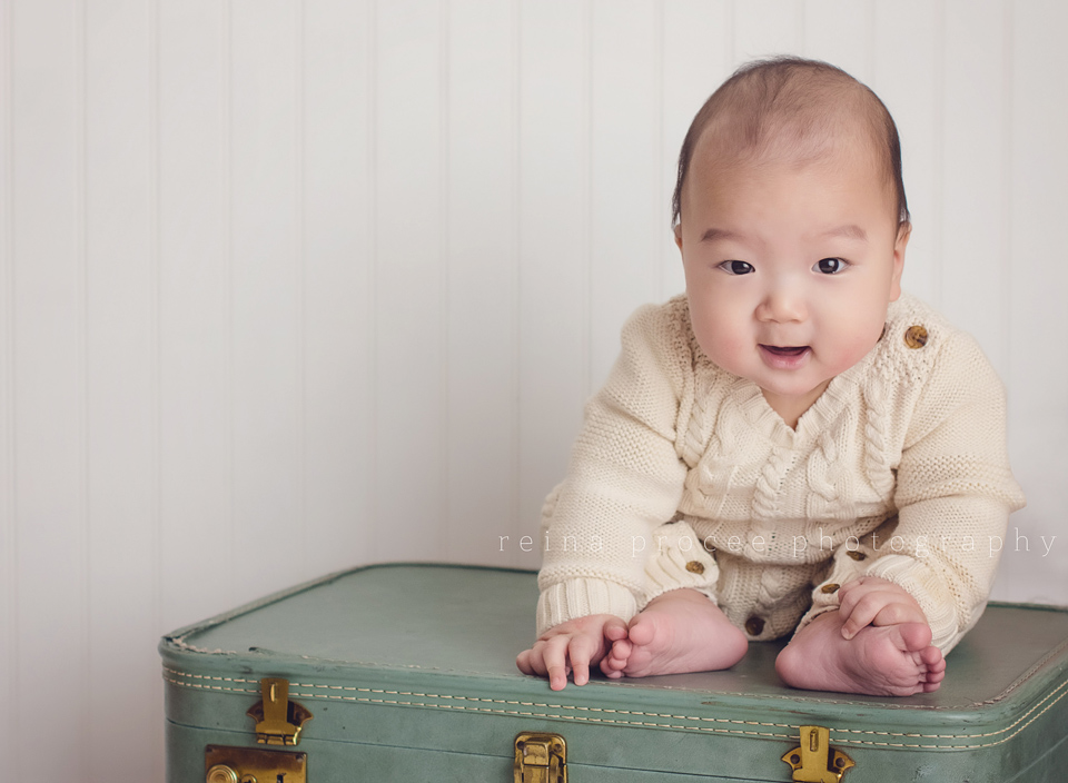 son sitting on green suitcase playing with toes