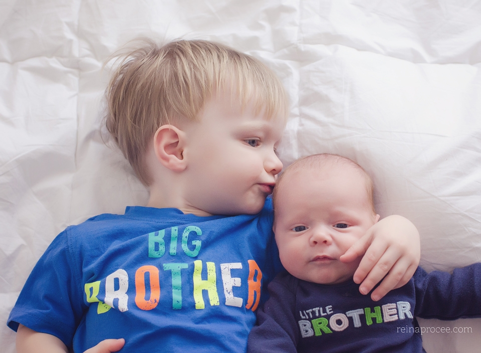 baby and brother lying down, big brother kissing little brother