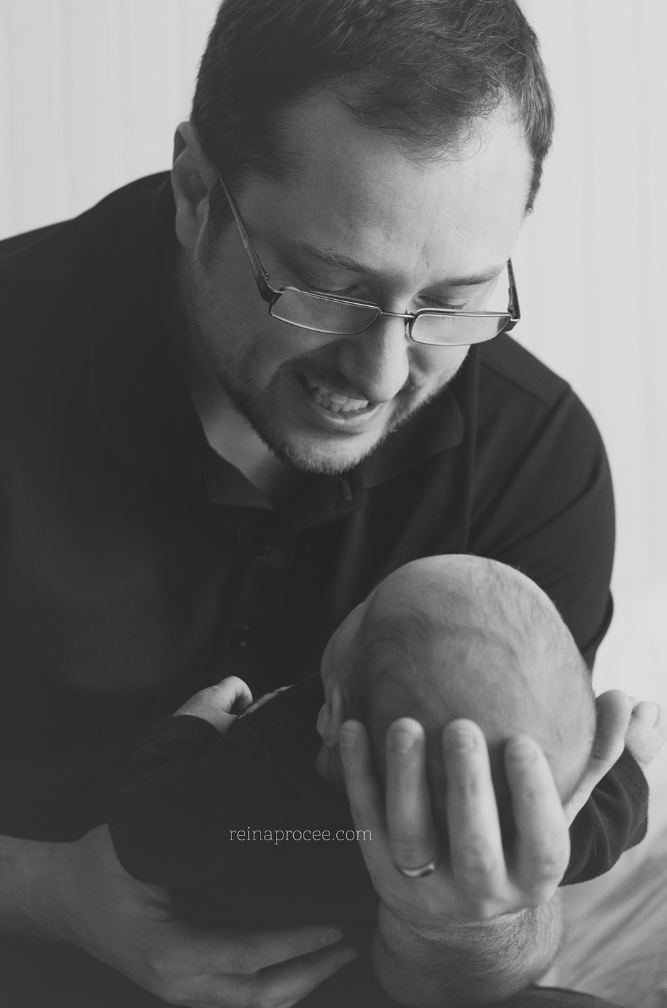 dad holding and smiling at newborn baby son