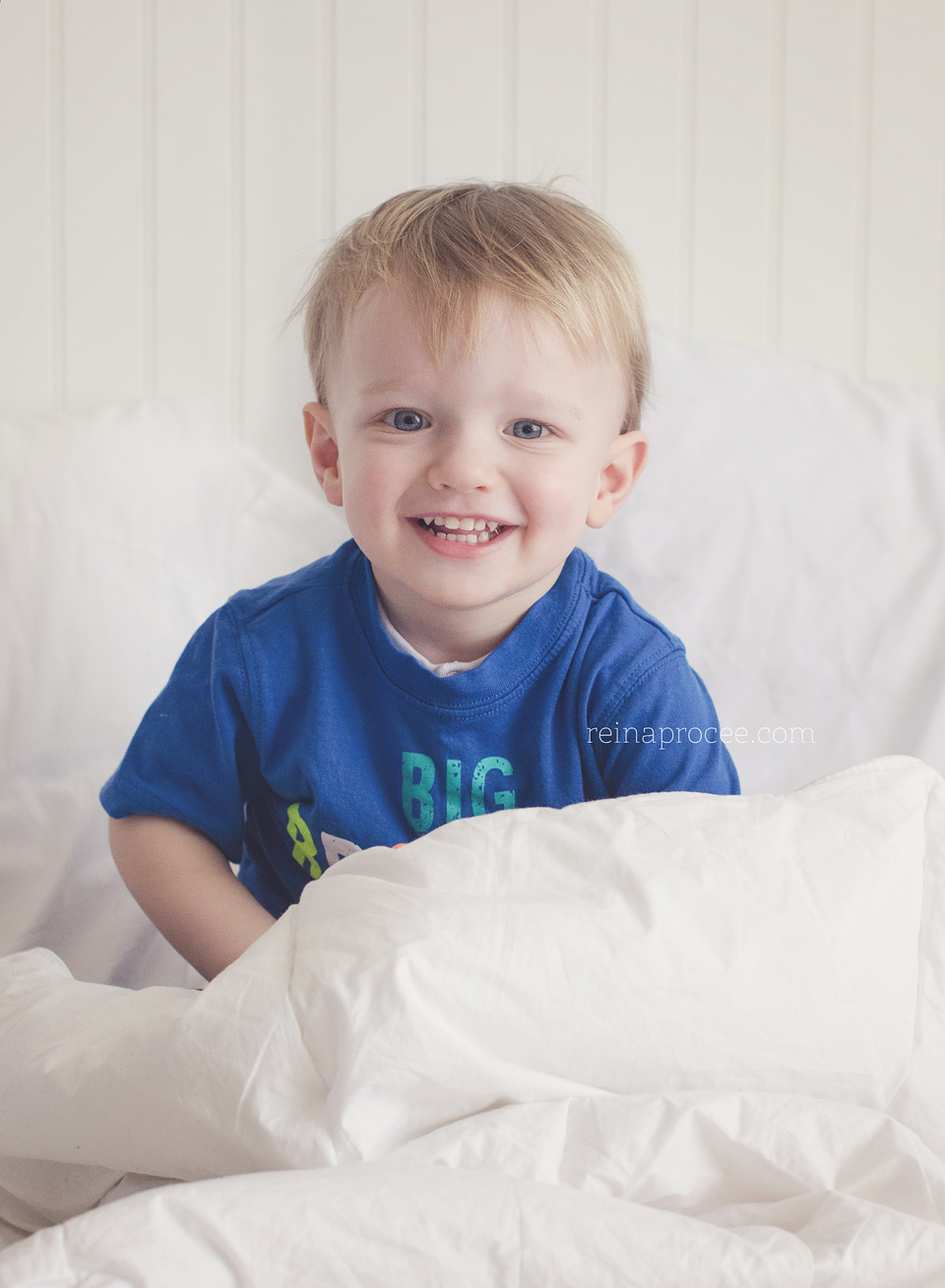 little boy in bed smiling wearing a blue shirt
