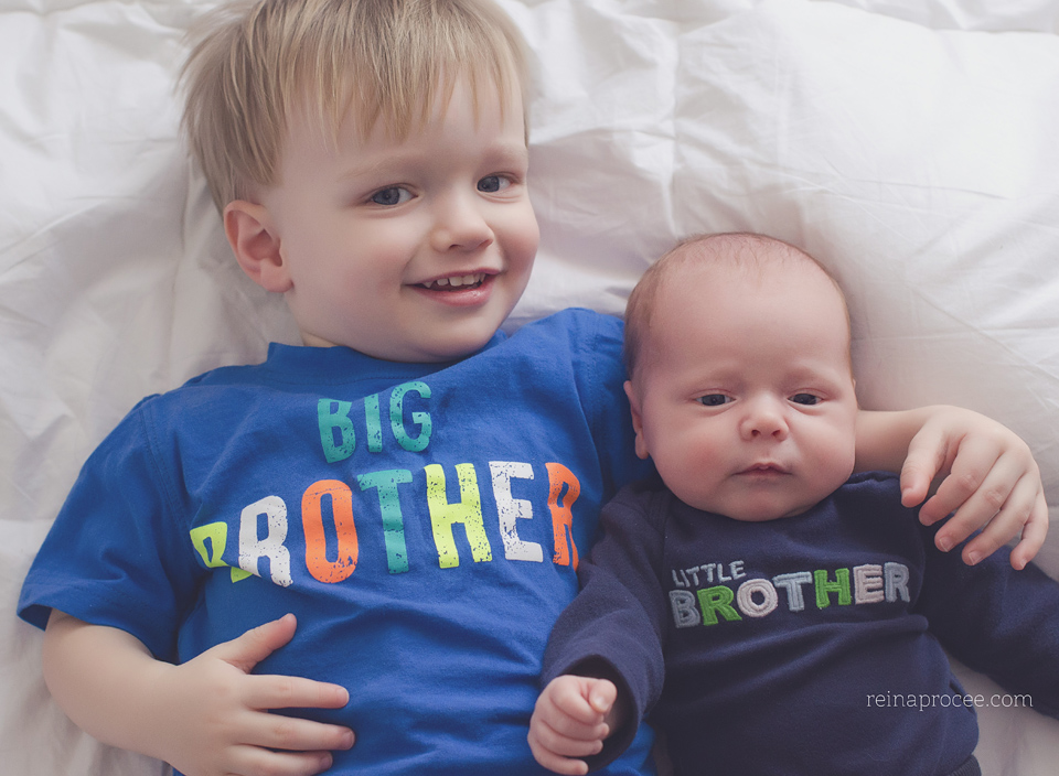 baby brother and newborn baby brother smiling at camera