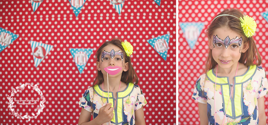 little girl in photo booth with face painted red and white polka dot backdrop