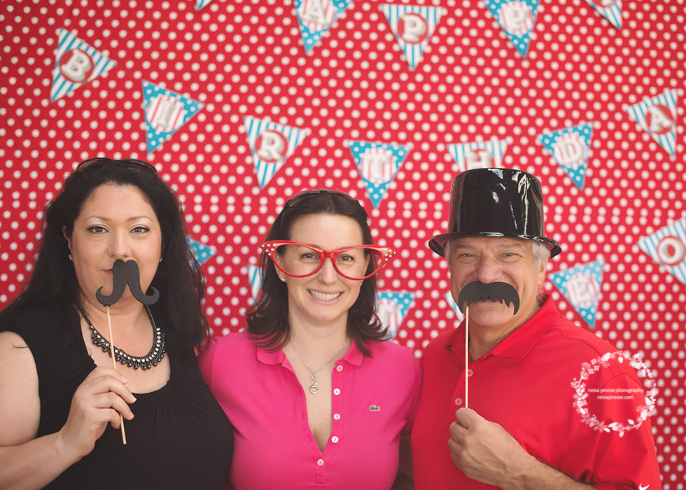 two women and one man in a photo booth red and white polkadot backdrop