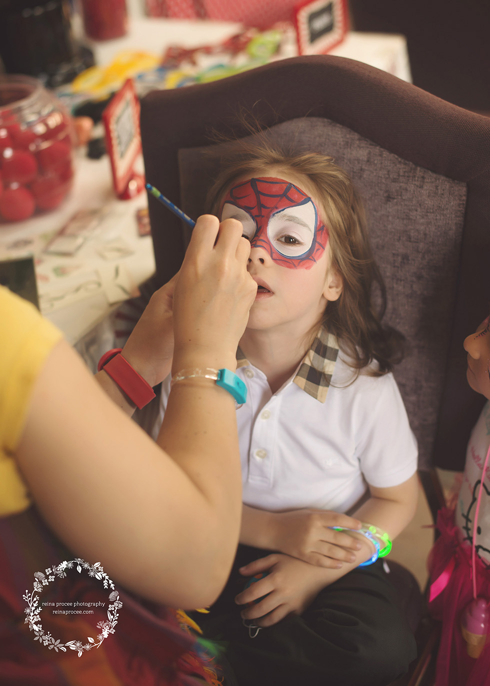little boy getting face painted like spiderman