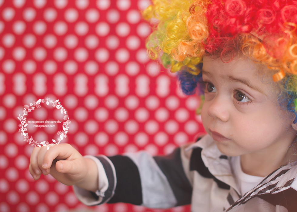 little boy with clown wig on red and white polka dot backdrop
