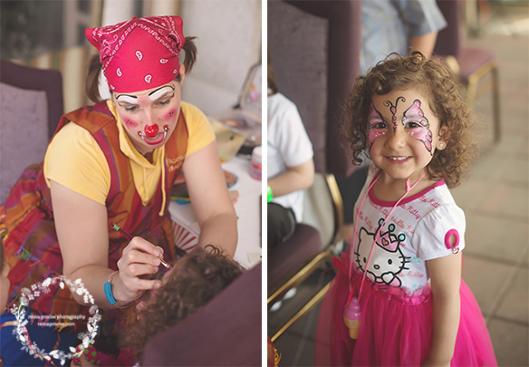 clown painting a little girl's face and little girl's butterfly painted face