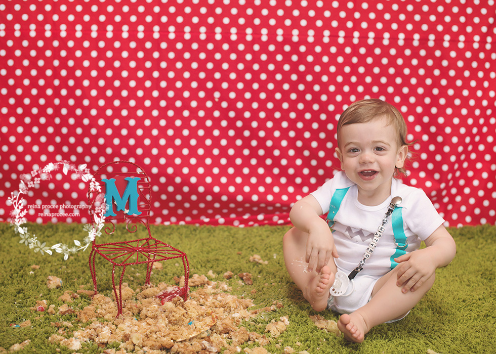 little boy with smashed cake red and white polka dot backdrop