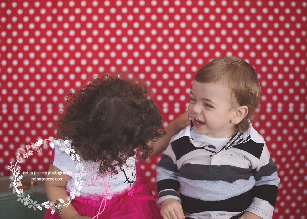 little boy and little girl red and white polka dot backdrop