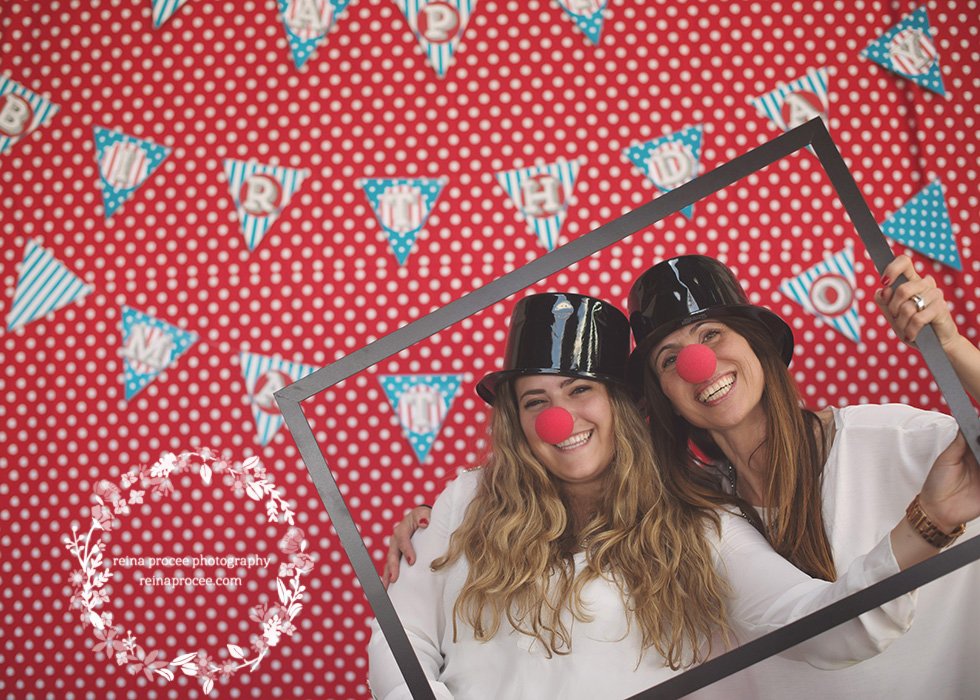 two women holding a frame with black top hats and clown noses red and white polka dot backdrop