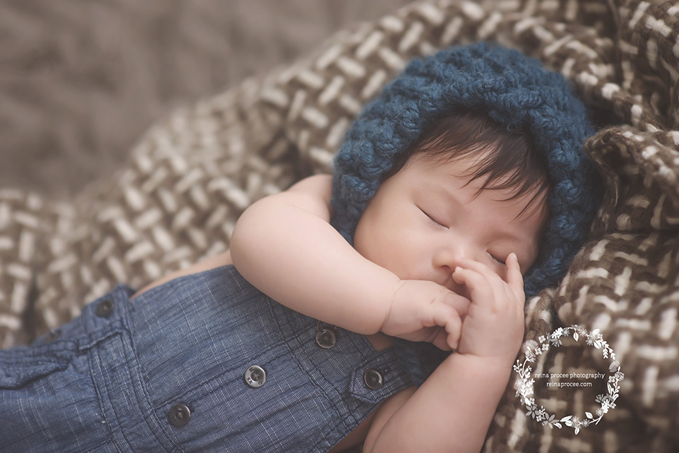 baby boy sleeping with hands in front of face with blue overalls and blue bonnet