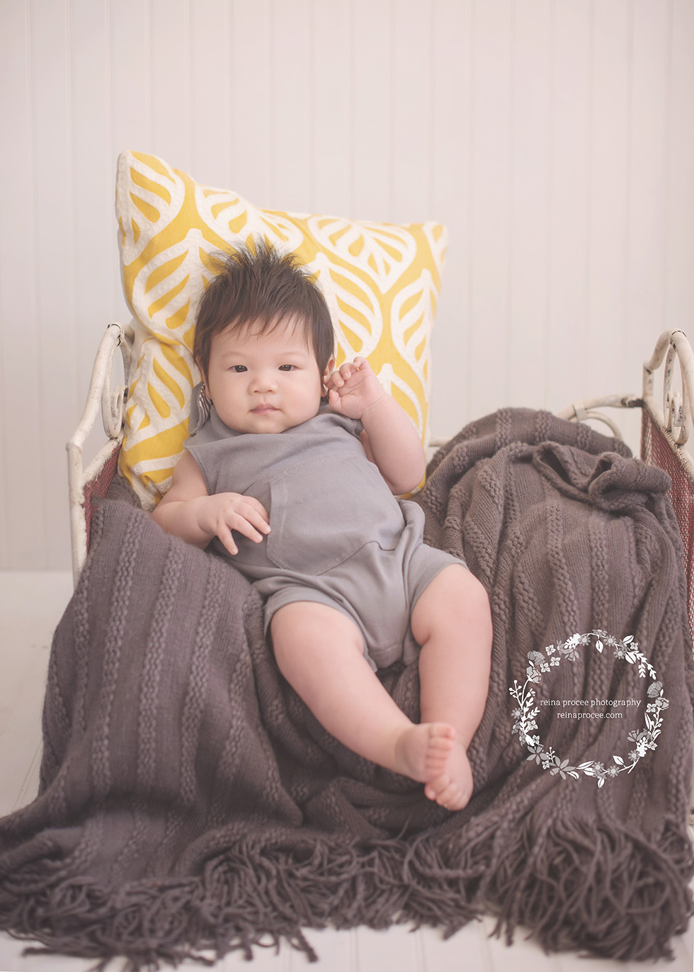 baby boy sitting on bed with grey blanket yellow pillow