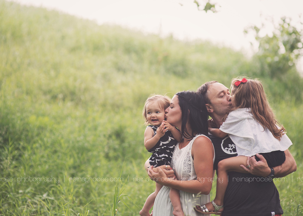 family hugging and kissing in a field