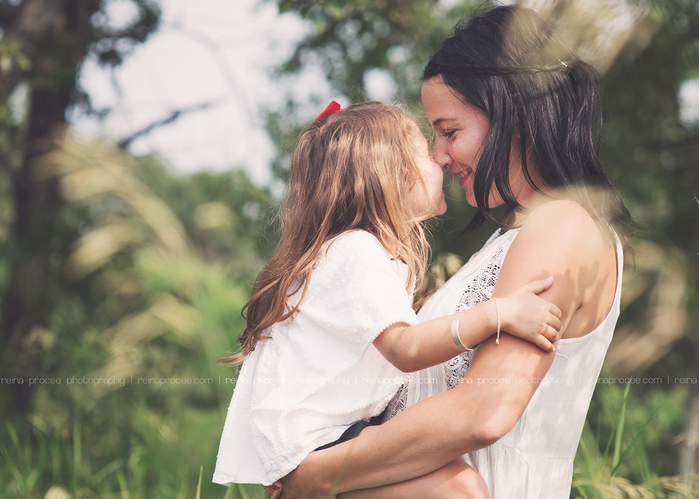 mom and daughter rubbing noses and hugging in a field