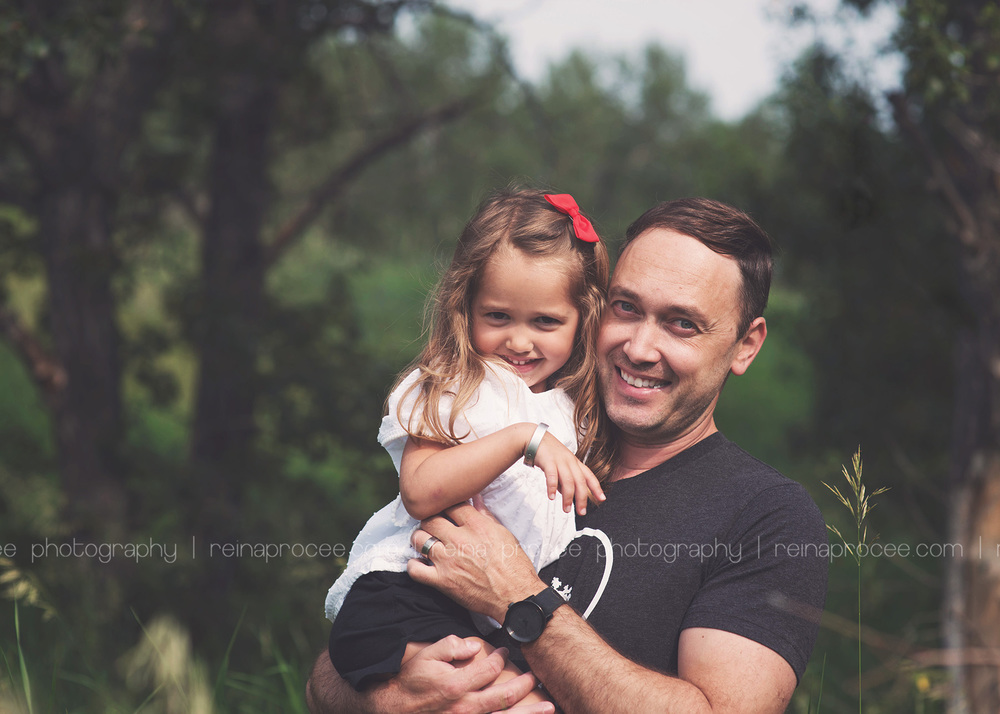 dad holding daughter and smiling at camera