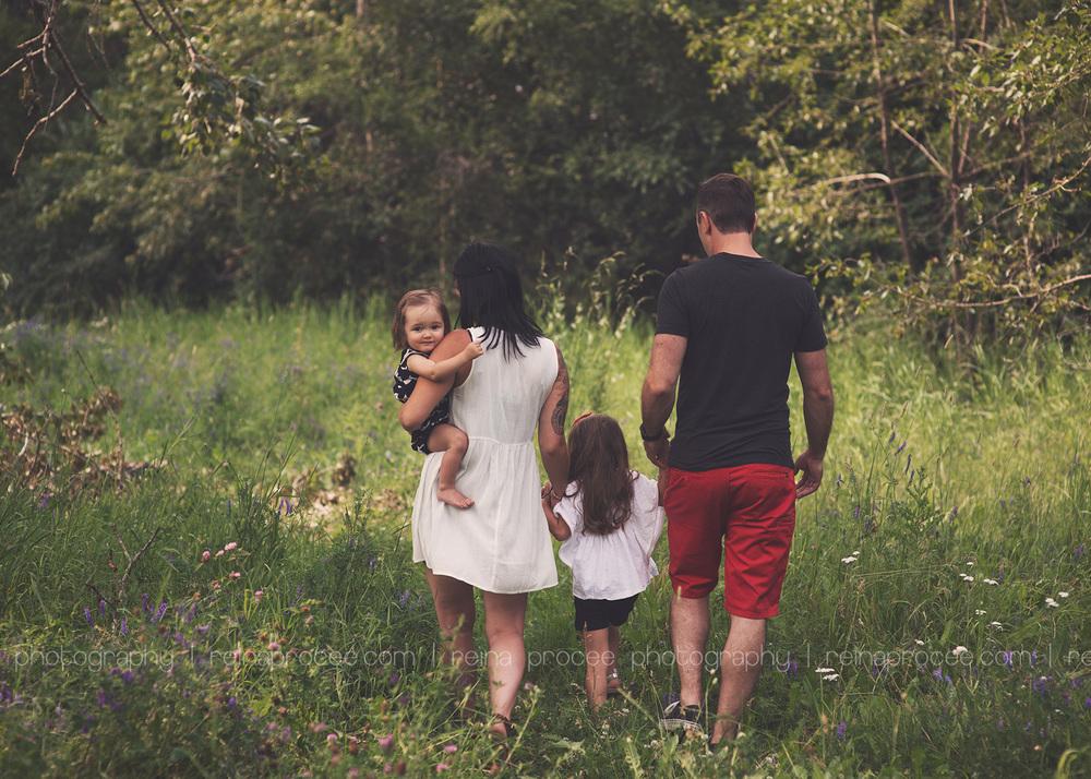 family walking away in a field