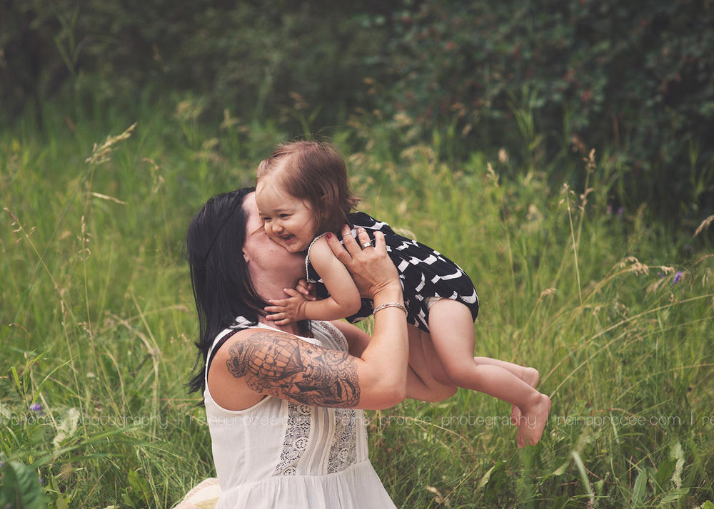 mom holding daughter up and kissing her cheek