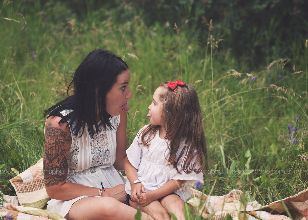 mom and daughter sticking out their tongues at each other in a field