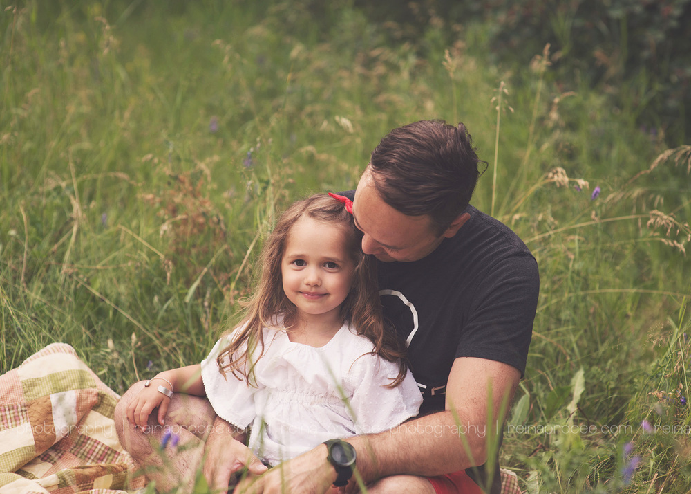 dad looking at daughter who is smiling at the camera