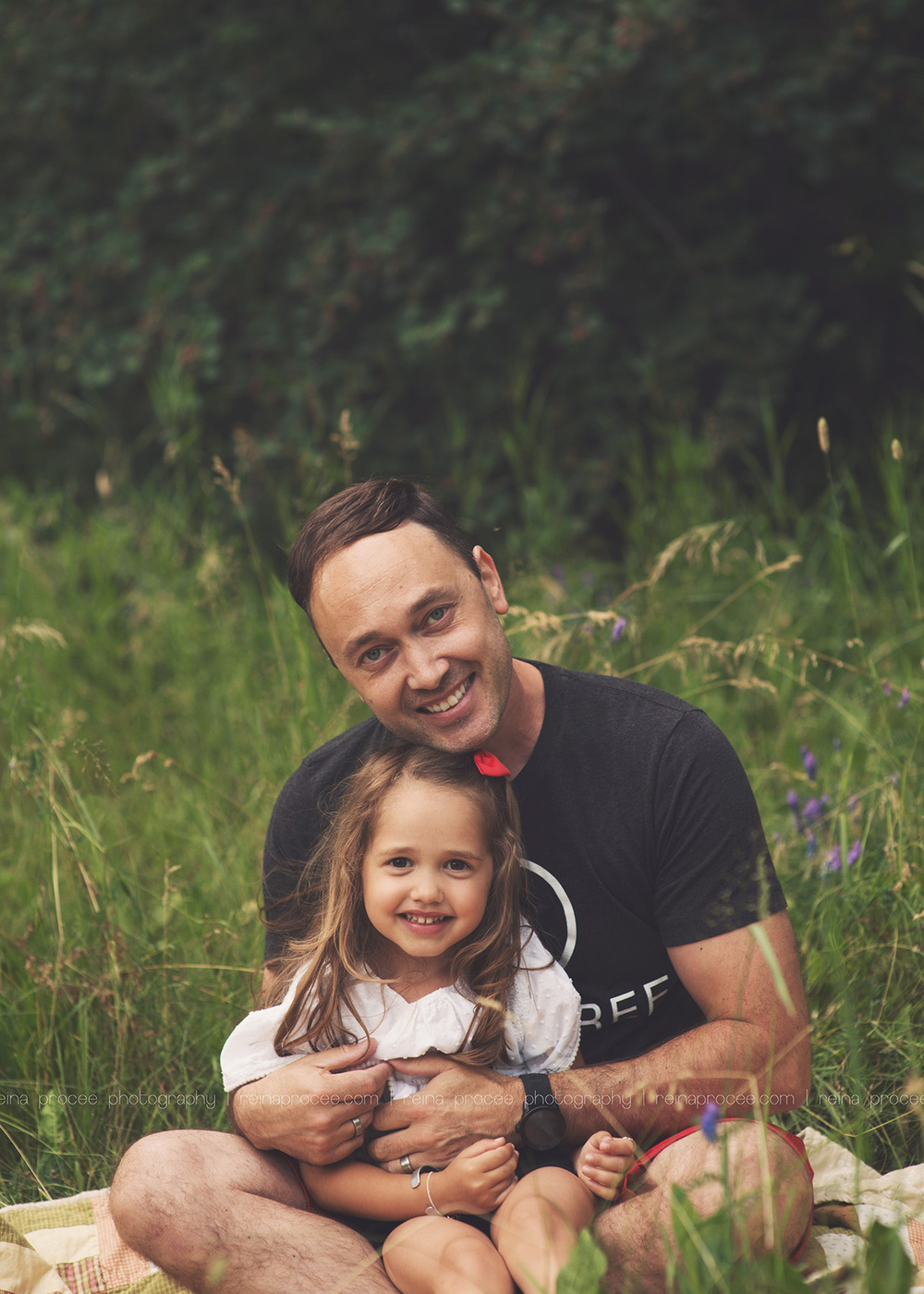 dad and daughter sitting in field smiling at camera