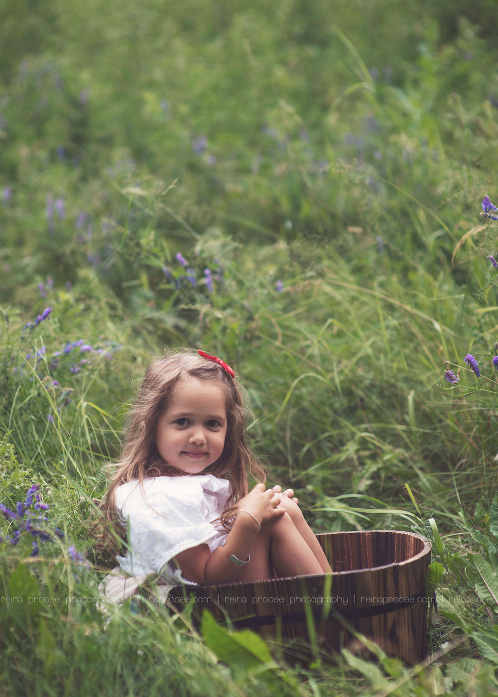 little girl siting in a bucket smiling at the camera