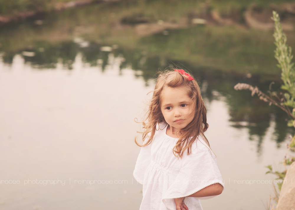 little girl posing in front of a lake