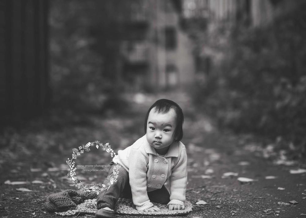little boy sitting in alley