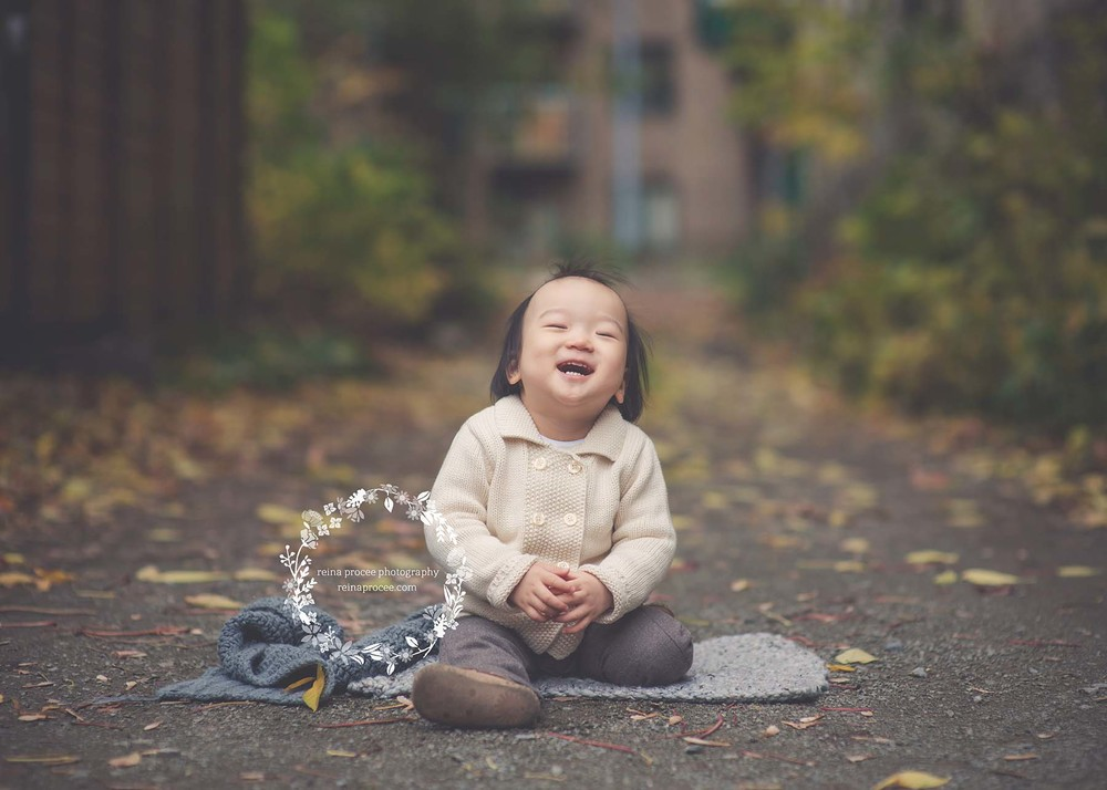 little boy sitting in alley laughing