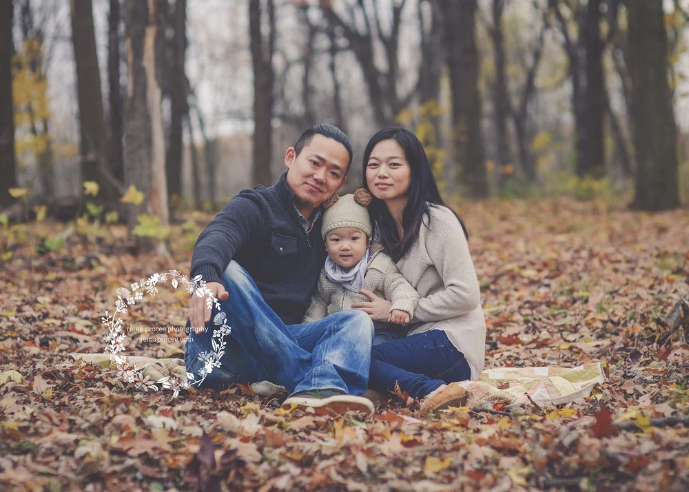 family sitting in fall leaves