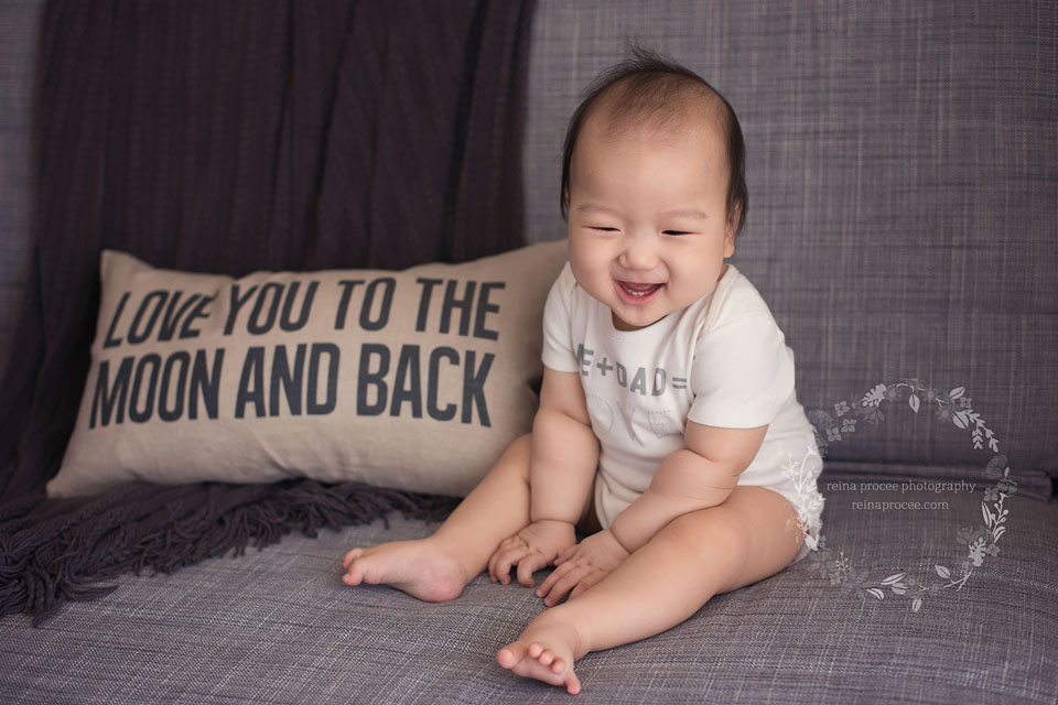 9 month old boy sitting on couch laughing
