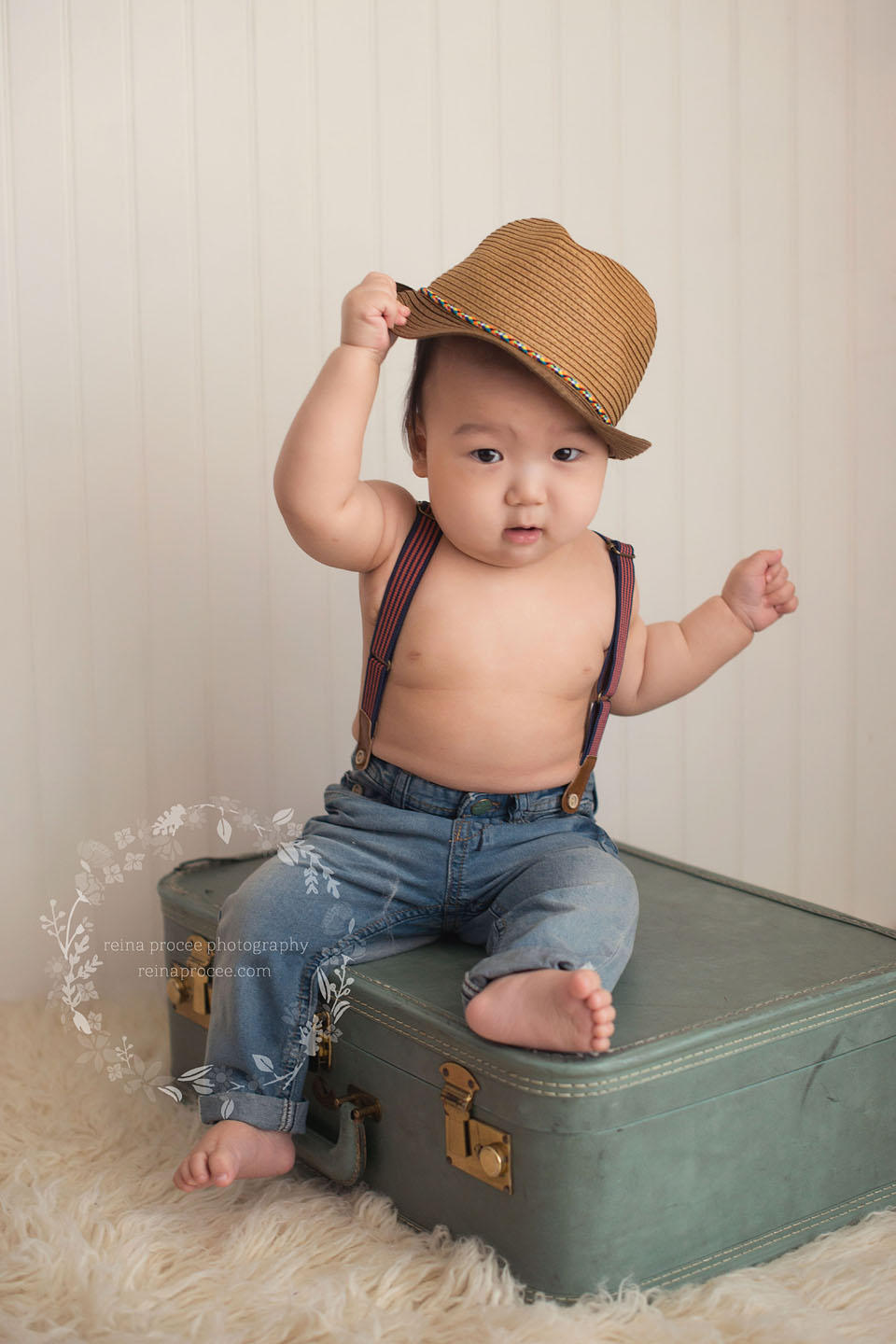 9 month old boy sitting on vintage suitcase playing with hat wearing jeans and suspenders