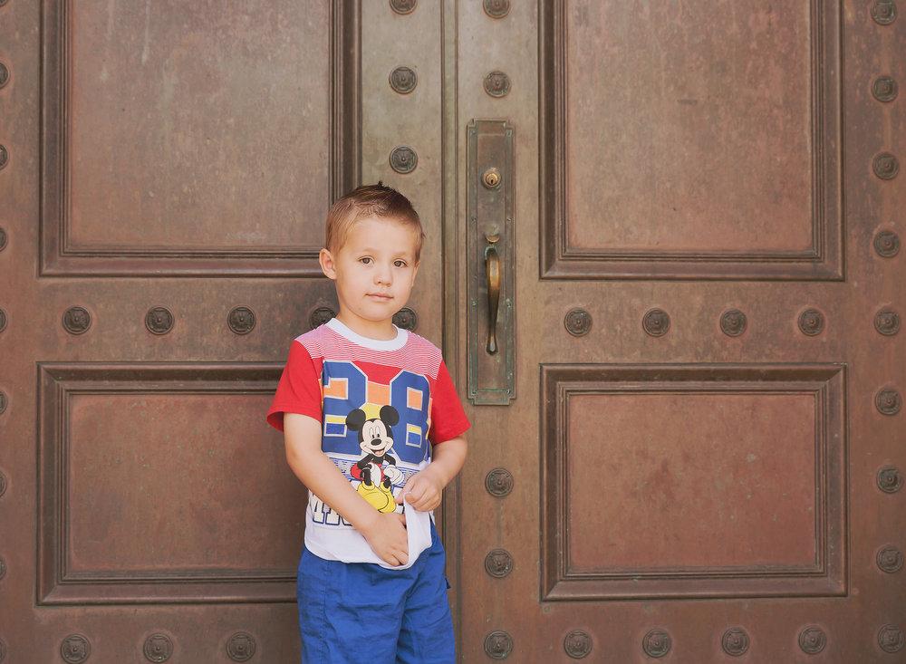 Child standing by bronze door