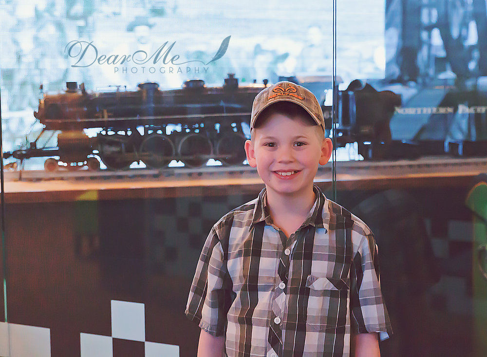 dear me photography bismarck faces of autism boy standing by model train