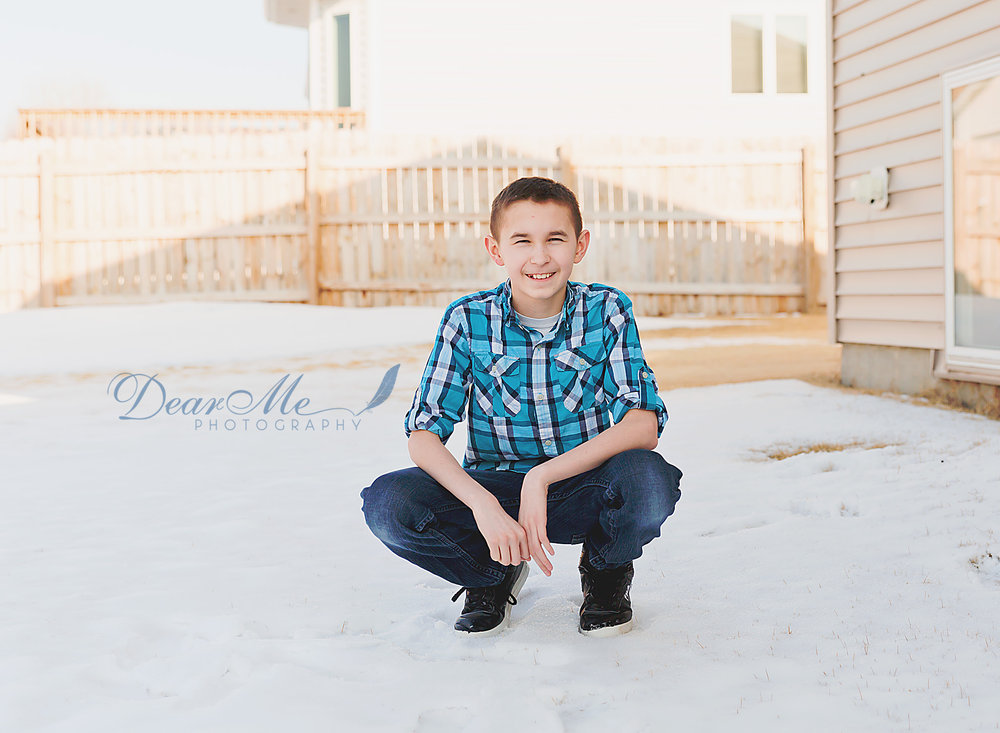 dear me photography mandan photographer boy crouching in the outside in a backyard