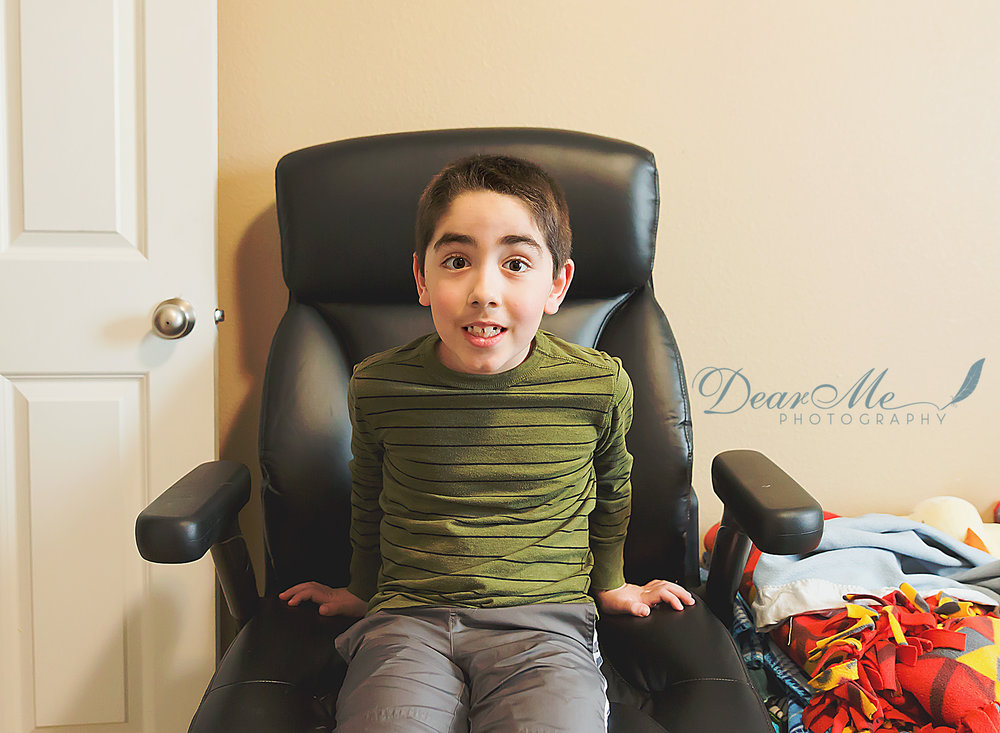 dear me photography bismarck photographer boy sitting in black roller chair in bedroom