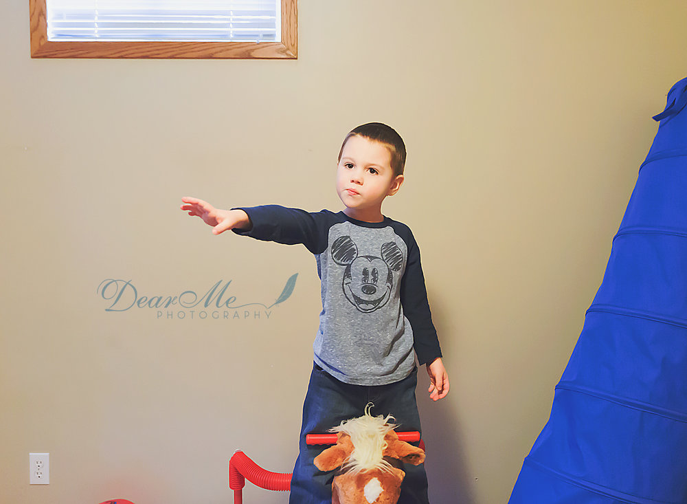 dear me photography bismarck nd boy standing on toy horse with his arm extended