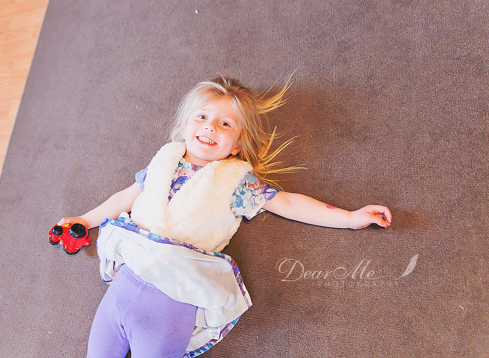 dear me photography mandan photographer girl laying on rug with toy car in her hand