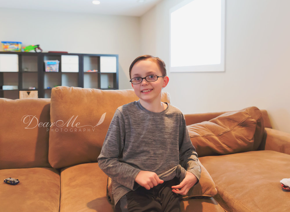 dear me photography bismarck photographer boy sitting on couch twirling his grey shirt
