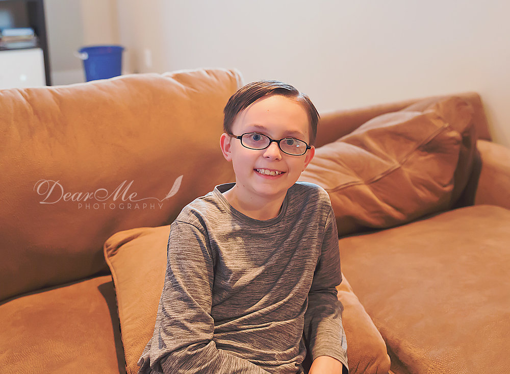dear me photography bismarck photographer boy in glasses sitting on couch leaned slightly back