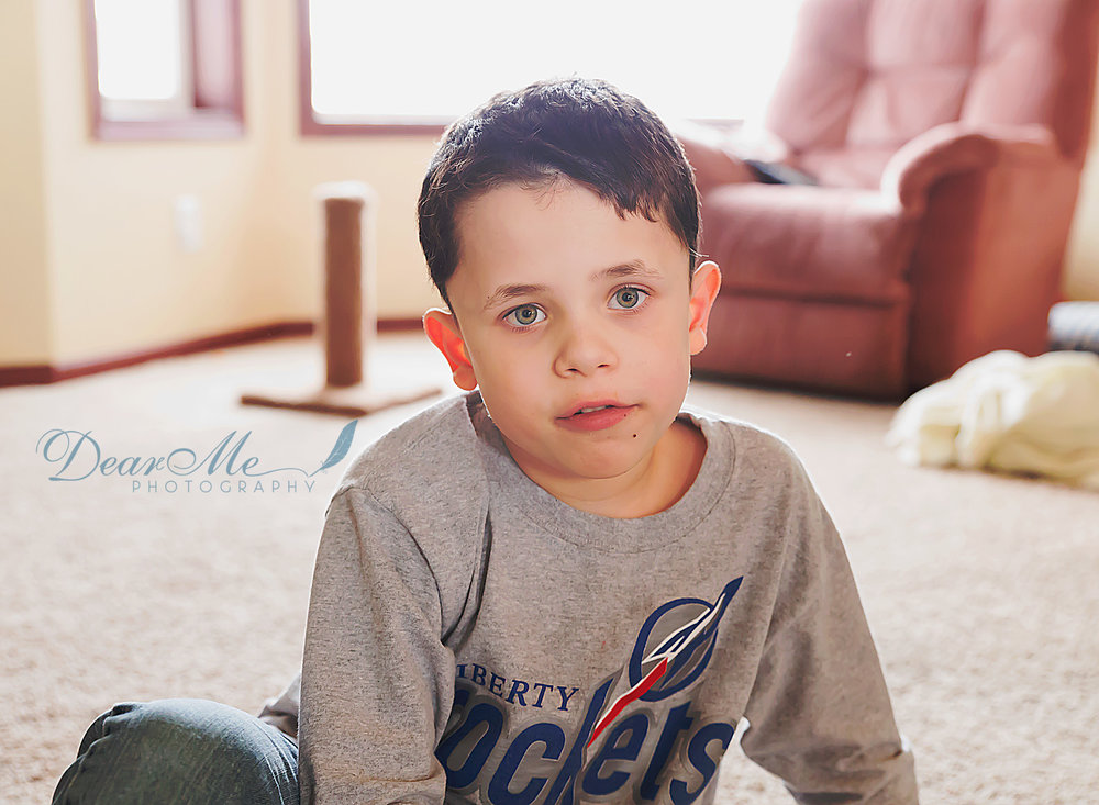 dear me photography bismarck photographer boy in grey shirt sitting on living room floor
