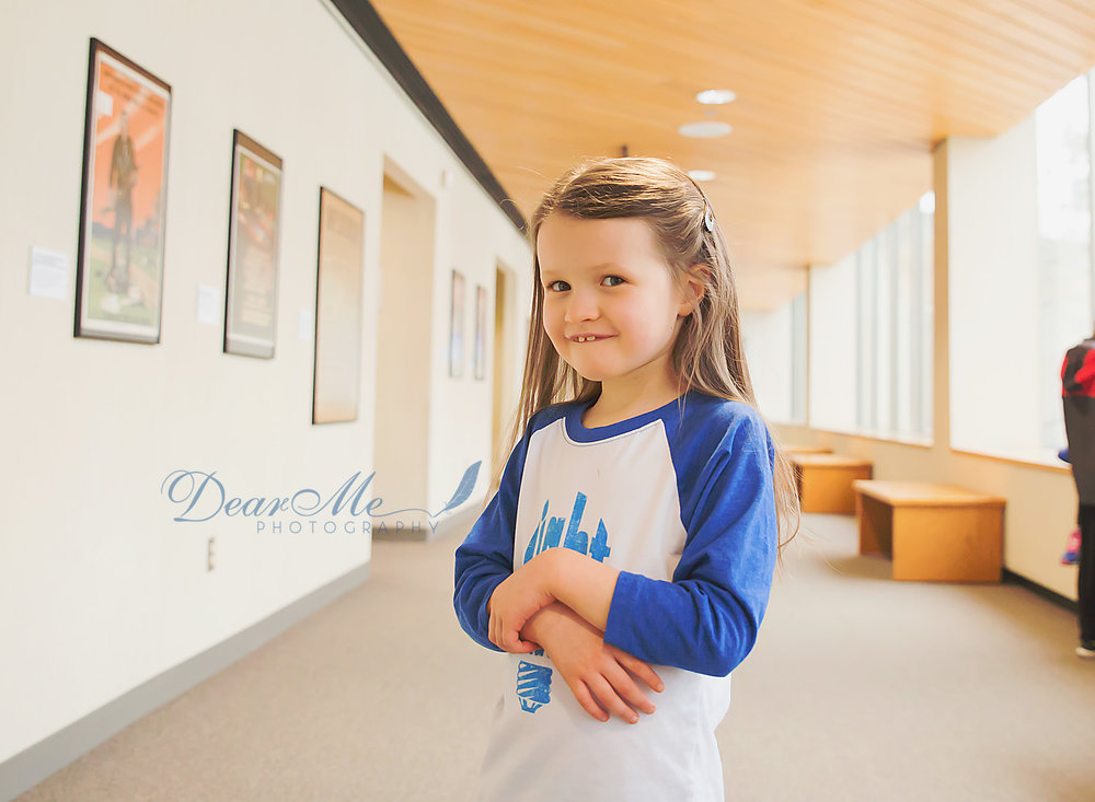 dear me photography bismarck photographer young girl in shirt with blue sleeves crossing her arms