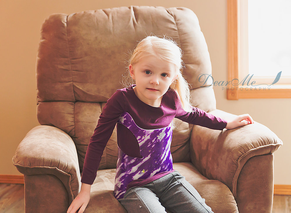 dear me photography mandan photographer girl in purple shirt sitting on recliner