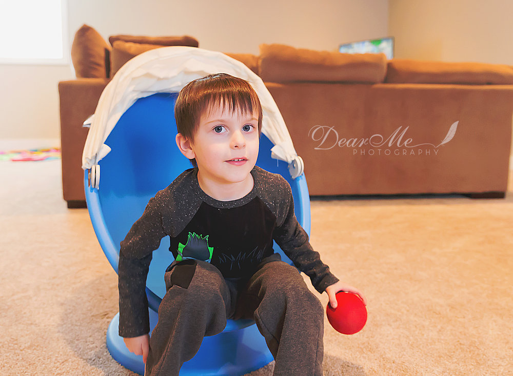 dear me photography bismarck child photographer boy sitting in blue egg chair