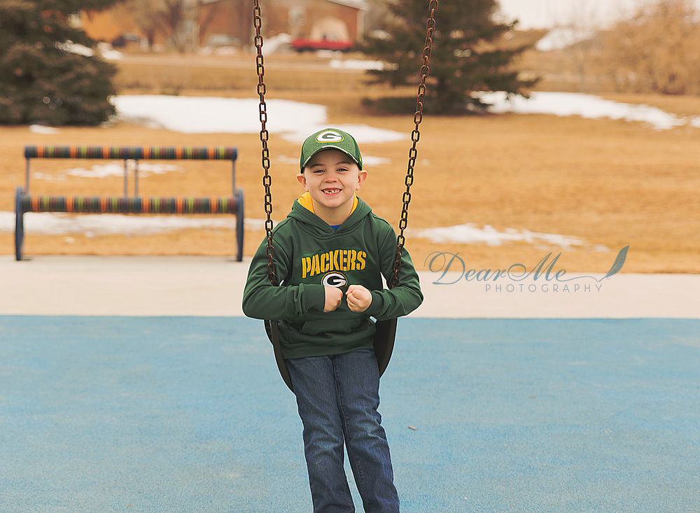 dear me photographer mandan photographer boy smiling on swing