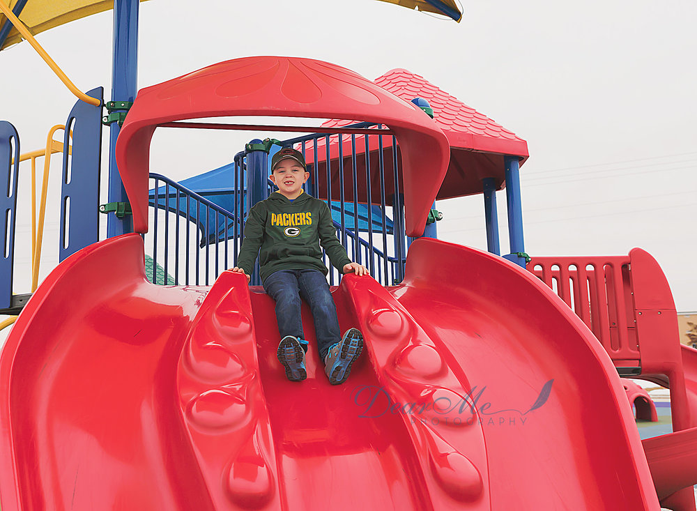 dear me photography mandan photographer boy on red slide
